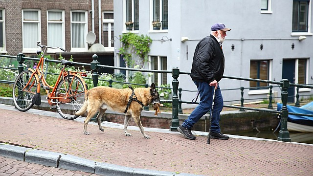 A man with a dog crossing the Lijnbaansgracht canal in Amsterdam