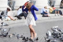 A girl walking through pigeons