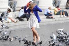 A girl walking through pigeons